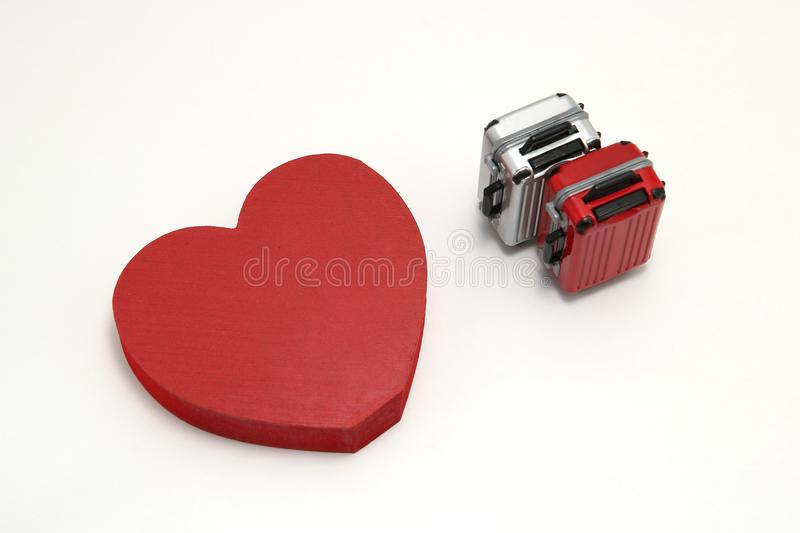 Miniature two suitcases and a red heart on white background. stock photos
