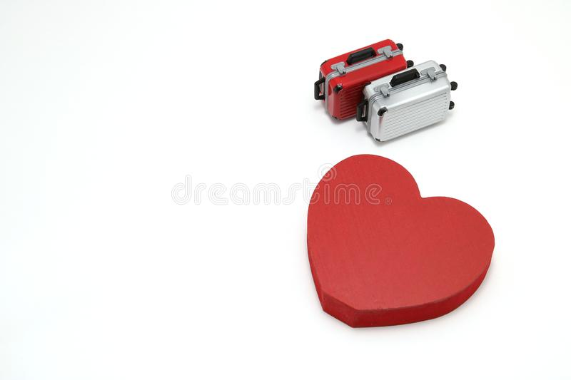 Miniature two suitcases and a red heart on white background. royalty free stock photos