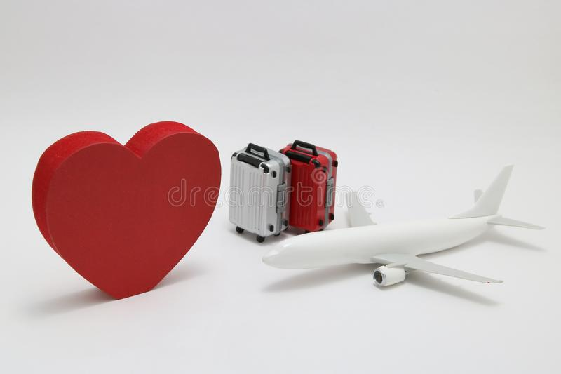Miniature two suitcases, toy airplane, and a red heart on white background. royalty free stock photo