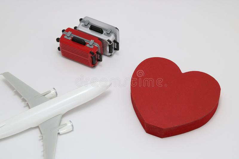 Miniature two suitcases, toy airplane, and a red heart on white background. stock photos
