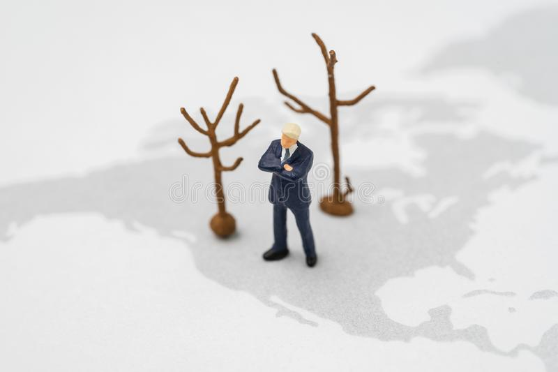 Miniature US America president leader standing on USA map with dried trees represent climate change or global warming policy.  stock photo