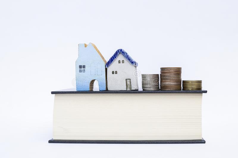 Miniature vintage house with stack of coin on think book isolate on white background stock photo