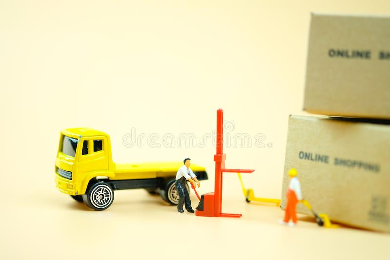 Miniature warehouse worker pulling a pallet truck with brown boxes prepare. online shopping concept stock image