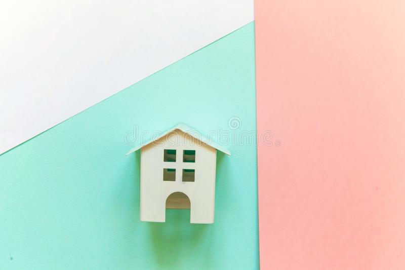 Miniature white toy house on white, pink and blue background. Simply flat lay design with miniature white toy house on white, pink and blue pastel colorful paper royalty free stock photos