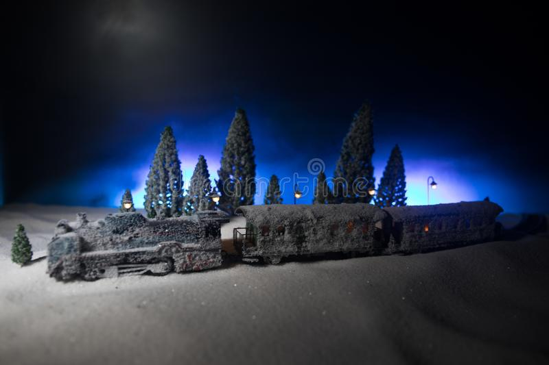 Miniature of winter scene with Christmas houses, train station, trees, covered in snow. Nights scene. New year or Christmas stock photos
