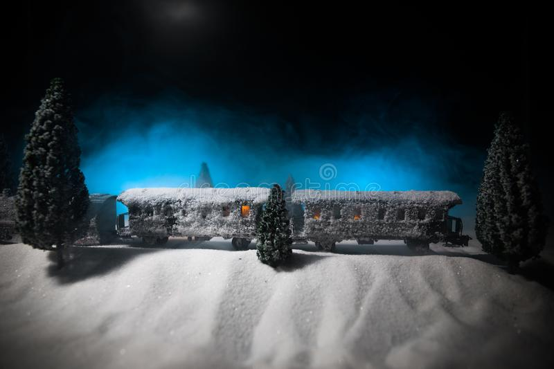 Miniature of winter scene with Christmas houses, train station, trees, covered in snow. Nights scene. New year or Christmas. Concept. Selective focus stock photos