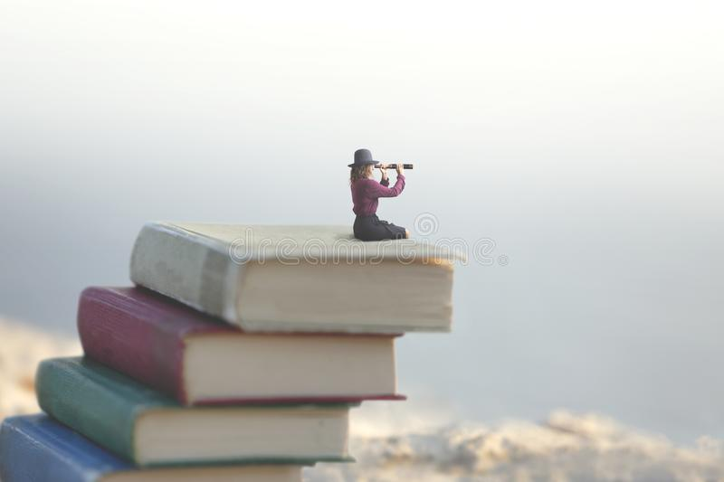 Miniature woman looks at the infinity with the spyglass on a scale of books stock photos