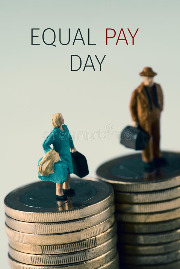 Miniature woman and man and text equal pay day. A miniature woman and a miniature man on the top of two equal piles of euro coins and the text equal pay day royalty free stock photography