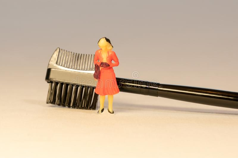 Miniature woman in orange dress next to black brow lash groomer brush. Beauty and Skin care concept stock photos