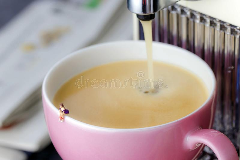 Miniature woman sitting at the edge of a cup stock image