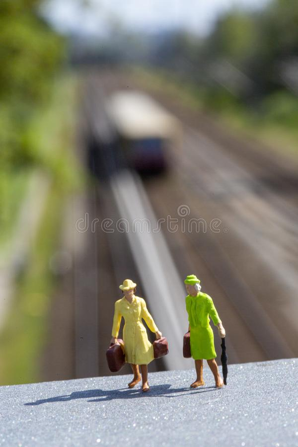 Miniature women with luggage standing on a platform ready to travel royalty free stock photography