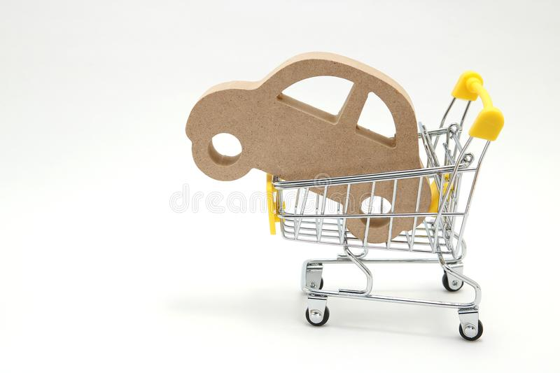 Miniature wooden car and shopping cart on white background. Concept of buying new car. royalty free stock image