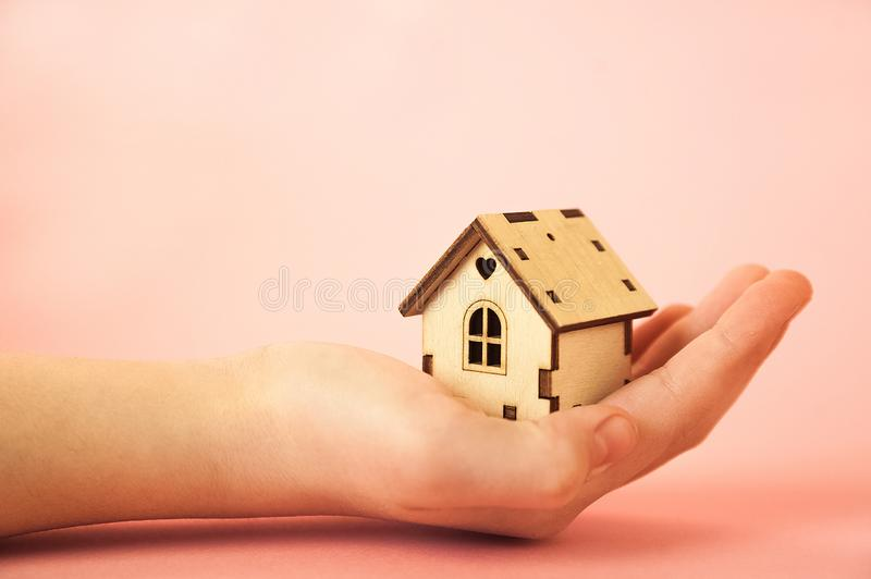 A miniature wooden house in children`s hands on a pink background closeup and copy space royalty free stock photo
