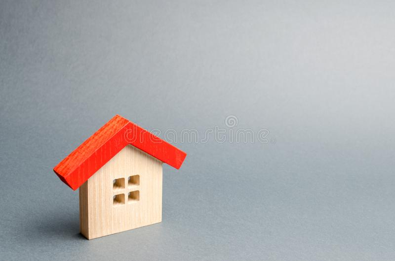 Miniature wooden house on a gray background. Real estate. Long-term rental apartments. Affordable housing for young families. Cheap property loans. Mortgage stock photo
