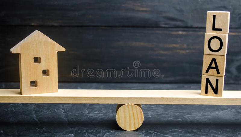Miniature wooden house and the inscription ` Loan `are on the scales. Buying a home in debt. Family investment in real estate and. Risk management concept. Loan royalty free stock photo