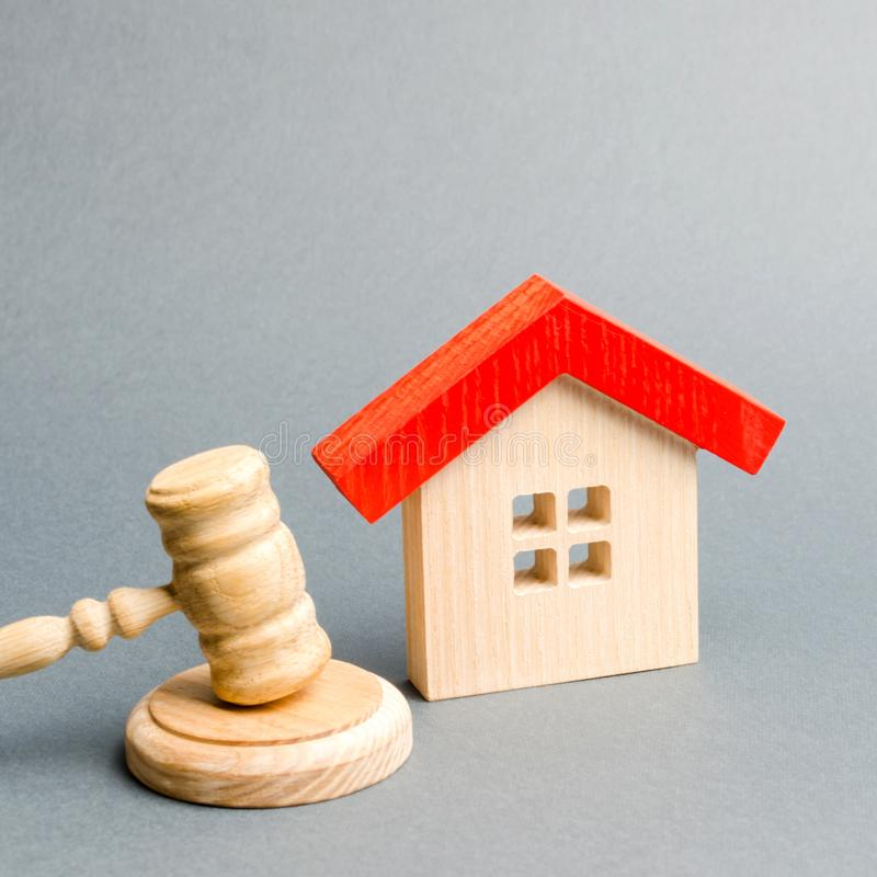 Miniature wooden house and judge`s hammer. The concept of resolving property disputes. Property alienation. Confiscated housing. royalty free stock photos