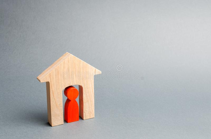 Miniature wooden house with a tenant inside. The concept of renting a house or apartment. Affordable housing. Mortgage. Home loan. Real estate and property royalty free stock image