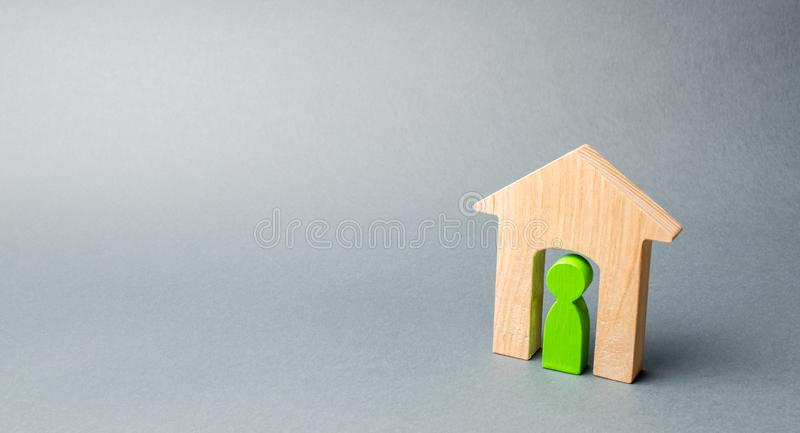 Miniature wooden house with a tenant inside. The concept of renting a house or apartment. Affordable housing. Mortgage. Home loan. Real estate and property royalty free stock photography