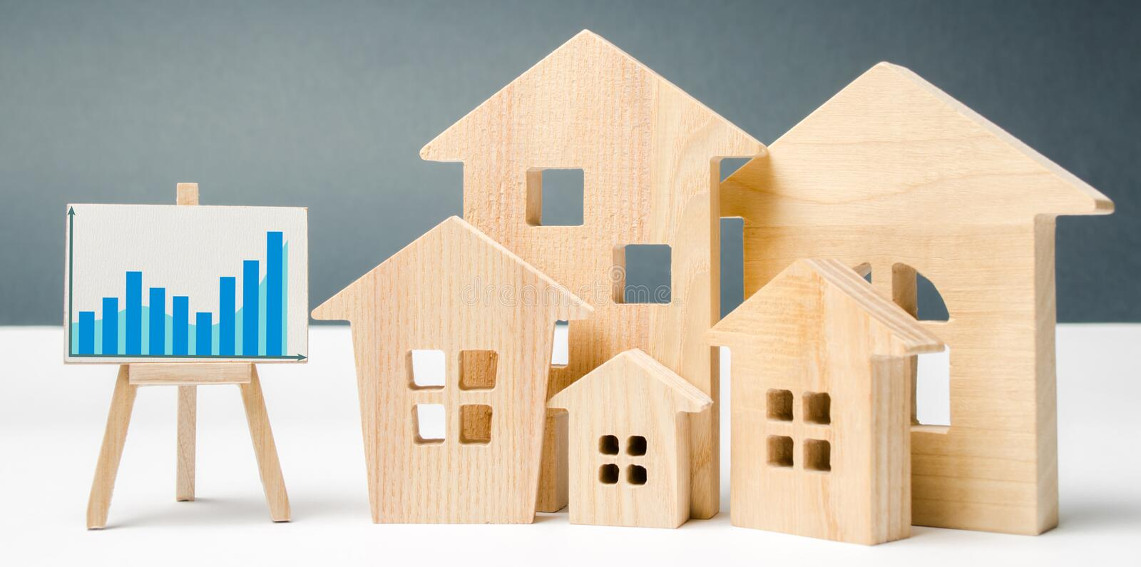 Miniature wooden houses and chart. Real estate. City. Agglomeration and urbanization. Real Estate Market Analytics. Demand for. Housing. Rising and falling home royalty free stock photography