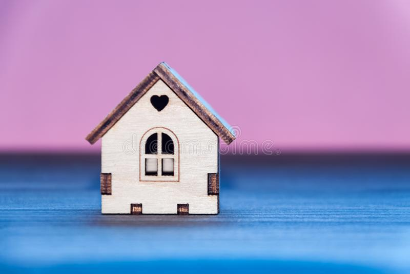 Miniature wooden toy house on a wooden table with a colored backgroundnd royalty free stock photo