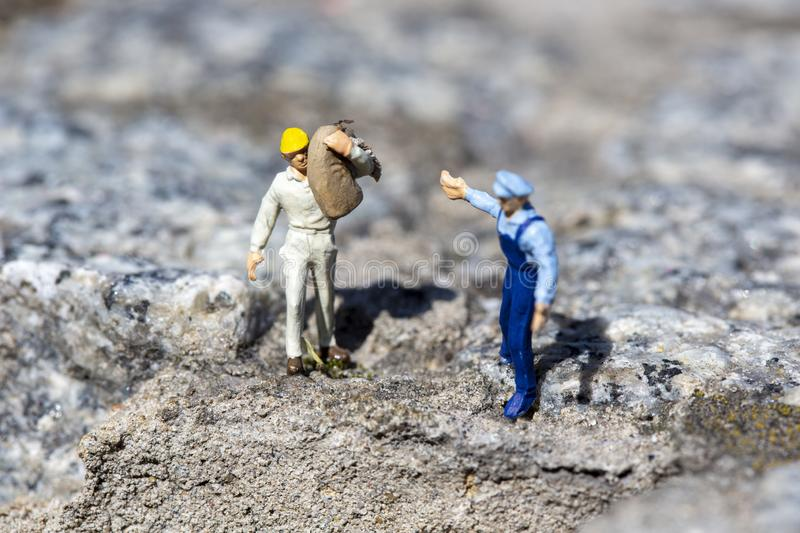 A miniature worker carrying a sand bag on a construction site royalty free stock image