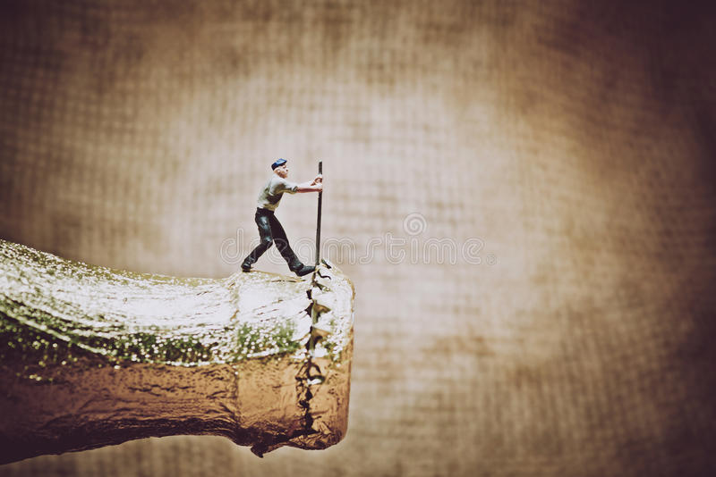 Miniature worker opening a beer bottle. Color tone tuned photo royalty free illustration