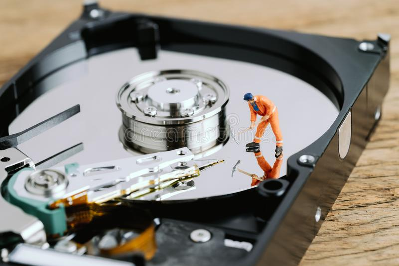 Miniature worker or professional staff digging on HDD, hard drive using as data mining, data restore or fixing and repair computer royalty free stock image
