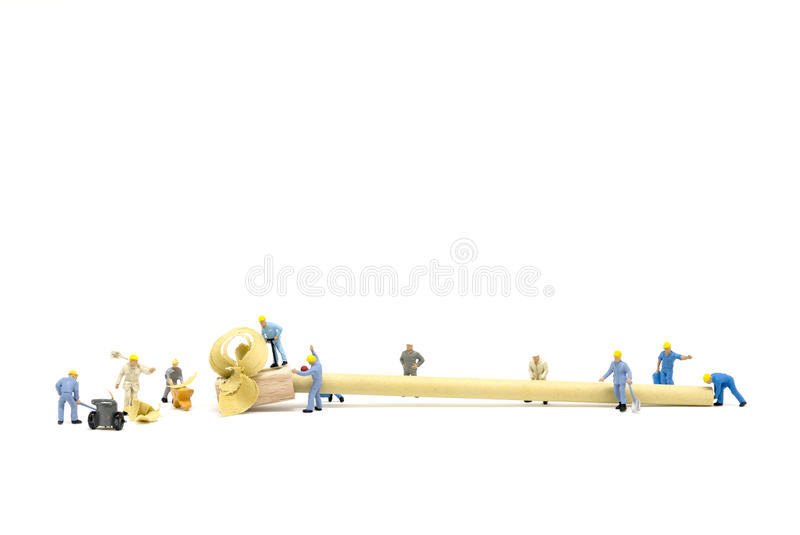 Miniature worker team sharpening a pencil royalty free stock photography