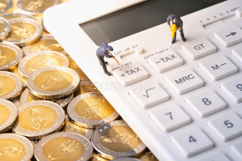 Miniature workers digging tax button on calculator on pile of coins. For business and taxation concept stock photos