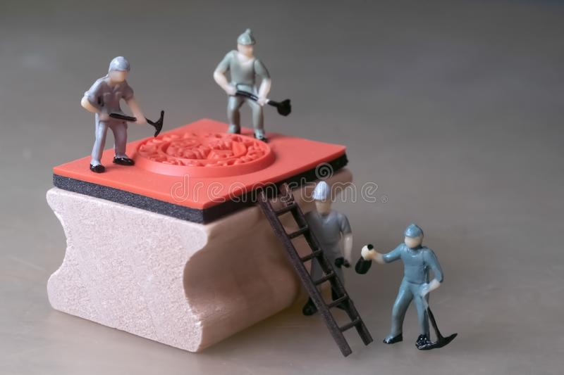 Miniature workers repaire rubber stamp stock images