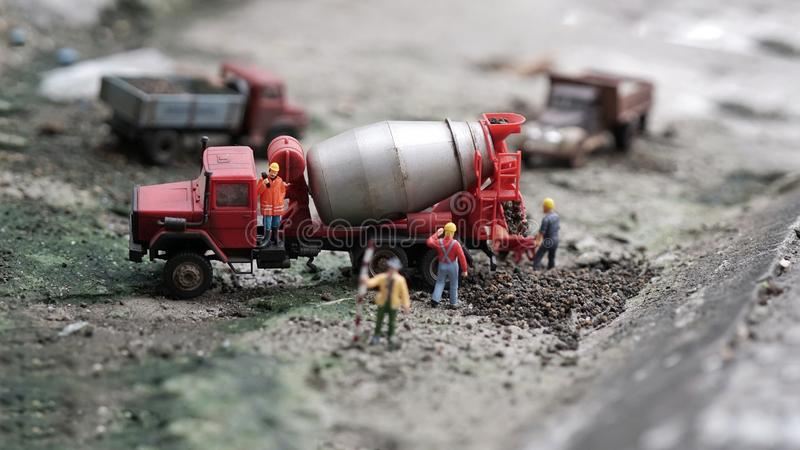 Miniature workers works with cement mixer truck stock images