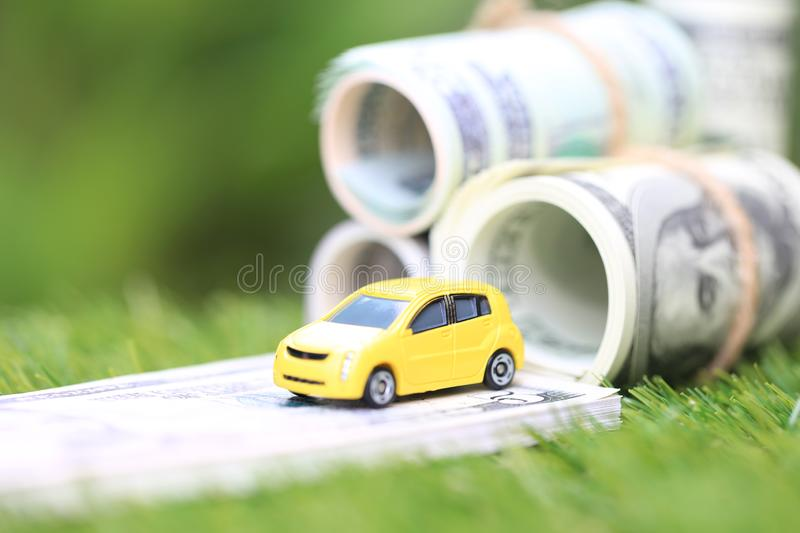 Miniature yellow car model with dollas banknotes on nature green background, Saving money for car, Finance and car loan,. Investment and business concept royalty free stock image