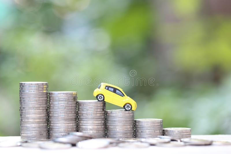 Miniature yellow car model on growing stack of coins money on nature green background, Saving money for car, Finance and car loan. Investment and business stock image