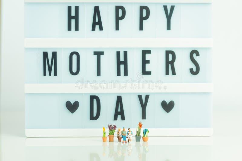 Miniaturfigürchen - 3 Generationen von Leuten auf weißem Hintergrund - glückliches Muttertageskonzept stockbild