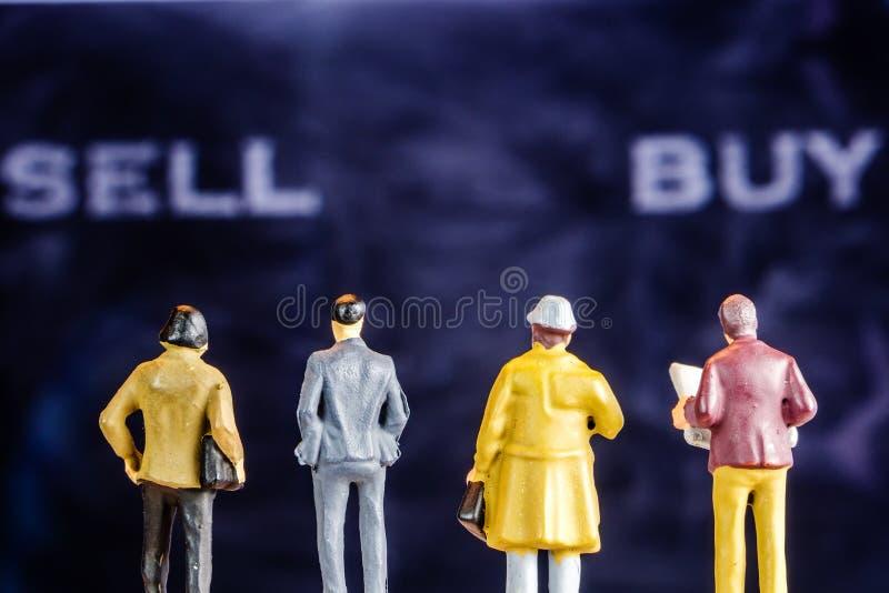 Miniaturfigürchen, die an den großen defocused Verkaufs- und Kaufwörtern die Hauptrolle spielt stockfotos