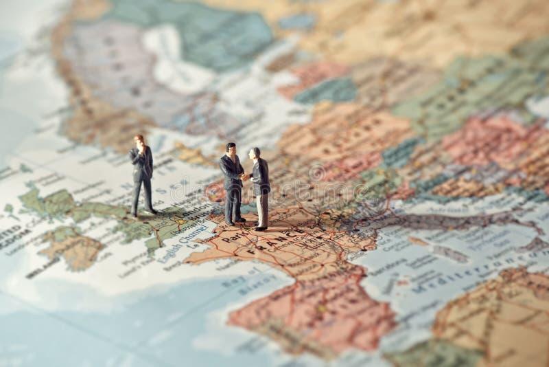Miniaturgeschäftsleute auf Karte von Europa Farbton abgestimmt stockfotos