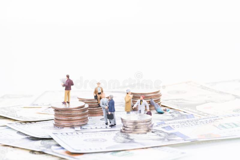 Miniaturgeschäftsleute auf US-Banknoten und -münzen stockfoto