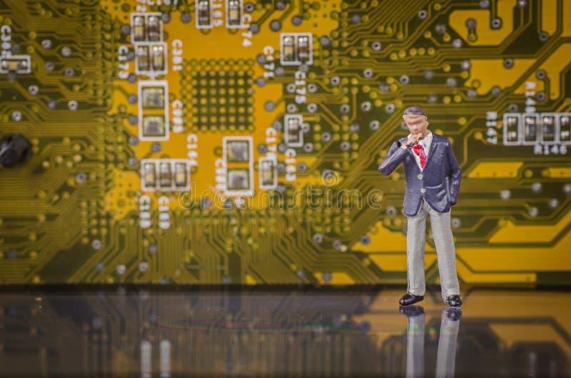 Miniaturgeschäftsmann auf modernem Leiterplattehintergrund stockfoto