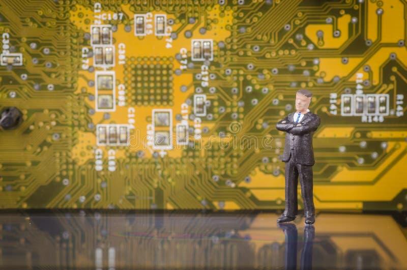 Miniaturgeschäftsmann auf modernem Leiterplattehintergrund stockfotografie