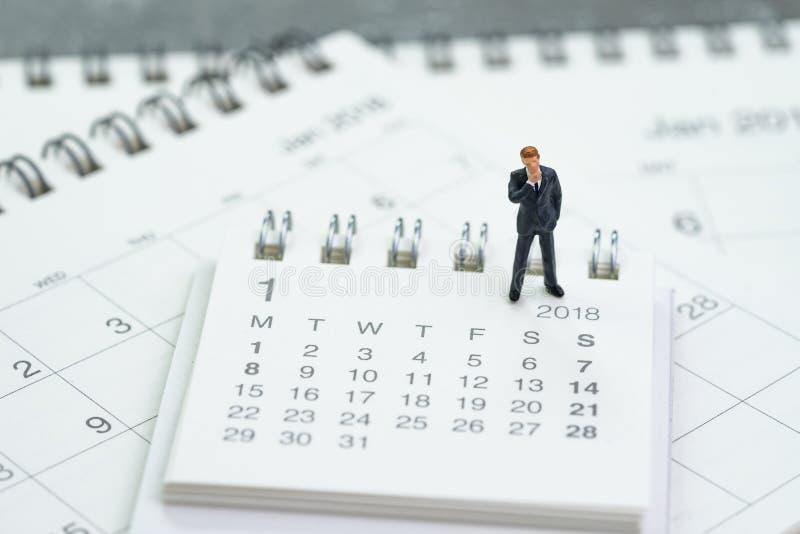 Miniaturgeschäftsmann, der auf Kalendern unter Verwendung a denkt und steht lizenzfreies stockbild