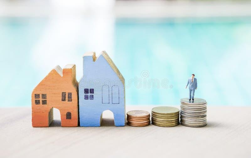 Miniaturgeschäftsmann, der auf Münzenstapel und -Holzhaus über unscharfem blauem Hintergrund steht stockbild