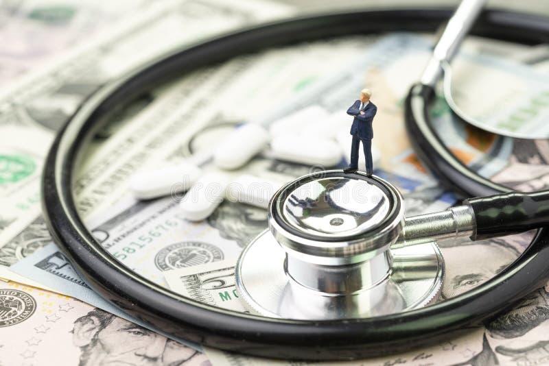 Miniaturgeschäftsmannstellung auf Stethoskop und weißen Tablettenpillen auf US-Dollar Banknoten, Gesundheitswesen, pharmazeutisch stockfoto