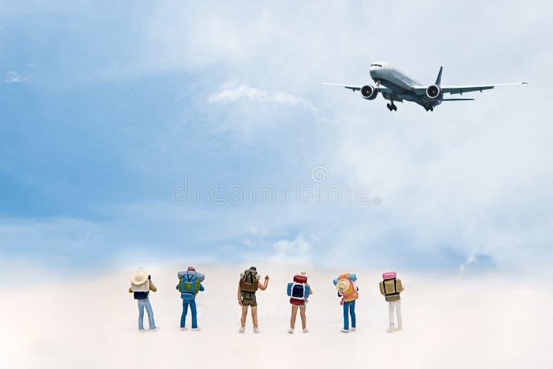 Miniaturgruppenwanderer und -reisender mit dem Rucksack, der zum Hintergrund des blauen Himmels des Flugzeuges steht und geht, stockfotografie