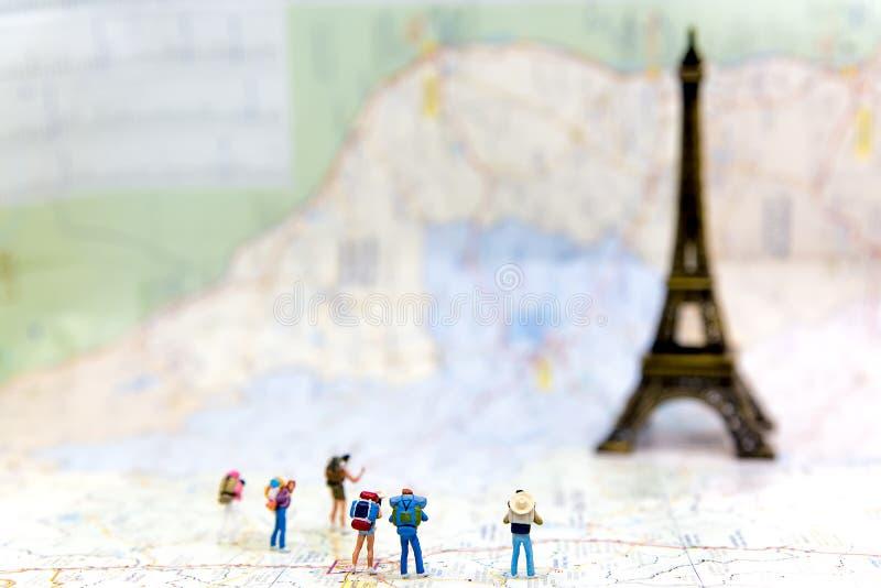 Miniaturgruppenwanderer und -reisender wandern Stellung auf Woldkarte für Reise Eiffelturm in Frankreich und auf der ganzen Welt, stockbilder