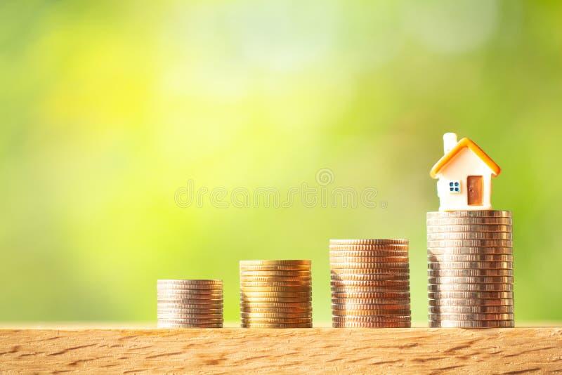 Miniaturhausmodell auf Münzenstapeln auf Grün unscharfem Hintergrund lizenzfreie stockfotos