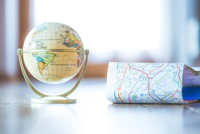 Miniaturkugelmodell auf einem rustikalen Holztisch Symbol für das Reisen lizenzfreies stockfoto