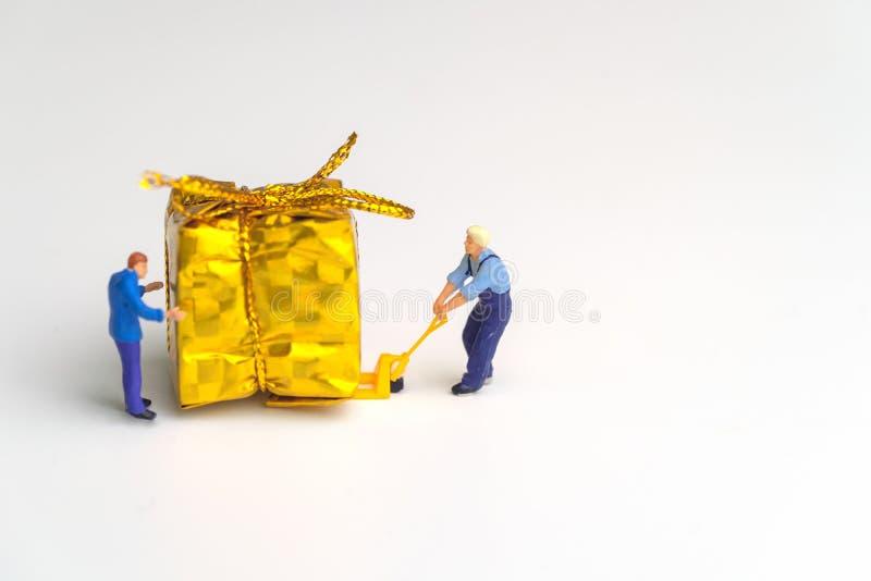 Miniaturkurier, der ein Goldgeschenk auf einem Gabelhubwagen für Weihnachtszeit auf weißem Hintergrund Versandkonzept bewegt stockfotos