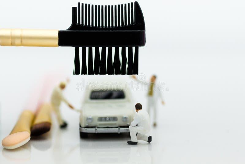 Miniaturleute: Arbeitskräfte bilden das Auto Bildgebrauch für das Säubern und Wartung, Geschäft Autocarkonzept lizenzfreie stockfotografie