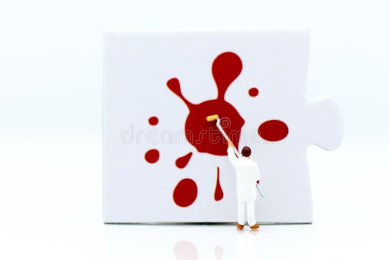 Miniaturleute: Arbeitskräfte malen Farbe auf dem Puzzlespiel Imag stockfotografie