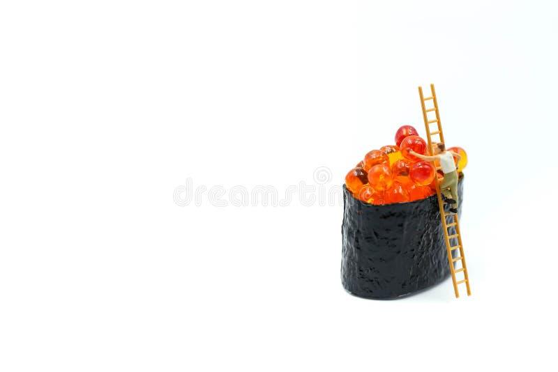 Miniaturleute: Arbeitskraft mit Lachsei auf Sushi nigiri Rolle O lizenzfreie stockbilder